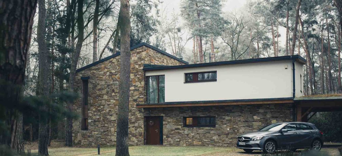 House in the forest with car parked besides